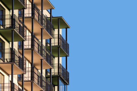 Modern flatgebouw met balkons tegen blauwe lucht aan advertentietekst