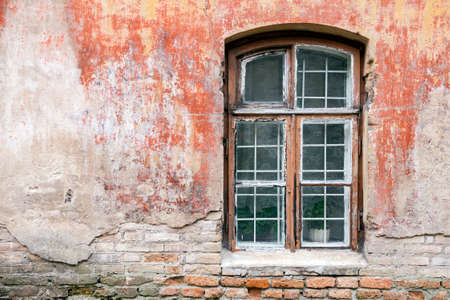 Weathered window with metal safety bars and old shabby building wall Stock Photo