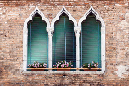 Traditional ancient gothic style window with flower pots in Venice, Italy Imagens
