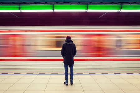 孤独な若い男がぼやけて背景で動いている電車と地下鉄の駅で後ろから撮影