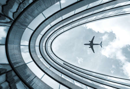 Low view blue colorized picture of modern architecture building with landing airplane in background