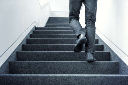 One man walking upstairs on staircase. Blue colorized picture