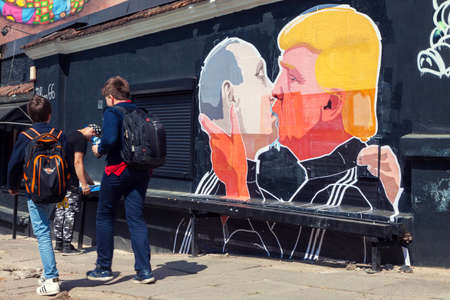 VILNIUS, LITHUANIA - MAY 13,2016: Mural artwork of Russian President Vladimir Putin and U.S. presidential hopeful Donald Trump kissing on the side of a barbecue restaurant in Vilnius, Lithuania.