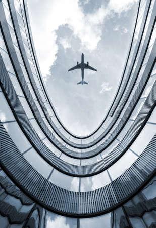 バック グラウンドで飛行機と現代建築低角度表示ブルー色付き画像。