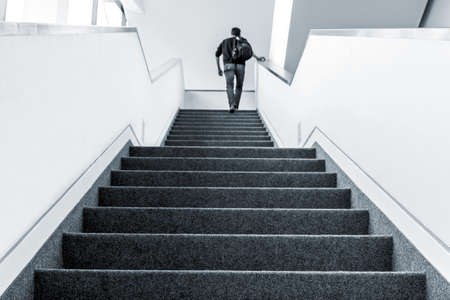 Image colorisée d'un homme marchant à l'étage, escalier intérieur