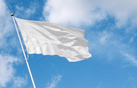 Blanco bandera ondeando en el viento contra el cielo nublado. Foto de archivo