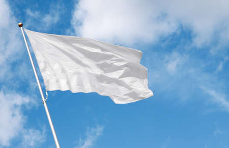 White flag waving in the wind against cloudy sky.