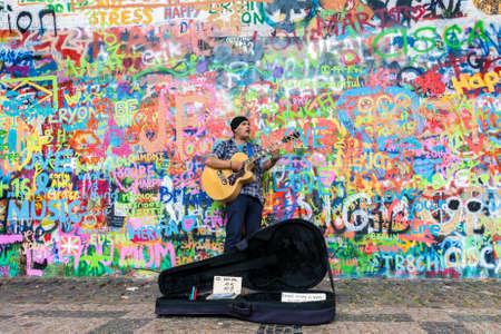 PRAGUE, TSJECHISCHE REPUBLIEK - 27 JUNI 2016: Straatkunstenaar die gitaar speelt bij de beroemde graafmuur van Lennon in de oude binnenstad van Praag, Tsjechië