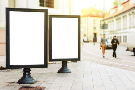 Two blank advertising billboards on the city street with pedestriants and sun glow Imagens - 69789132