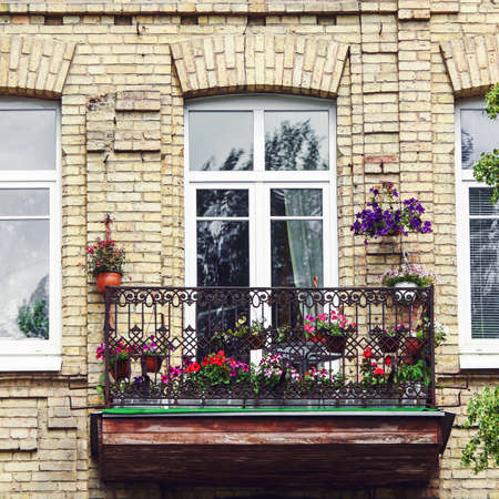 Classic style balcony with flowers at summertime Stock Photo