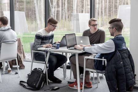 VILNIUS LITHUANIA - APRIL 23 2016: Young male students sitting and studying in coworking space at Vilnius University library, Lithuania Editorial