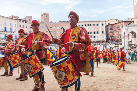 SIENA, ITALY - JUNE 29, 2016: Men musicians with drums in historical colorful costumes celebrating at traditional Palio horse race parade in Siena, Italy