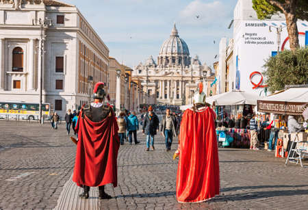 ROME, ITALY - DECEMBER 08, 2017: Two actors dressed as Roman Empire soldiers in streets of Rome, Italy, with St. Peters basilica in background 新聞圖片