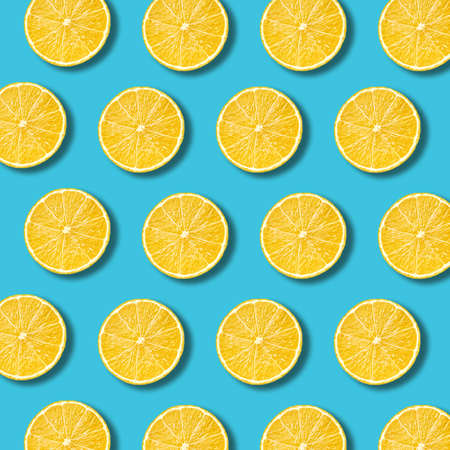 Lemon slices pattern on vibrant turquoise color background. Minimal flat lay food texture  Stock Photo