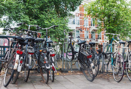 Group of old weathered vintage bicycles parked on the street in Amsterdam, Netherlands
