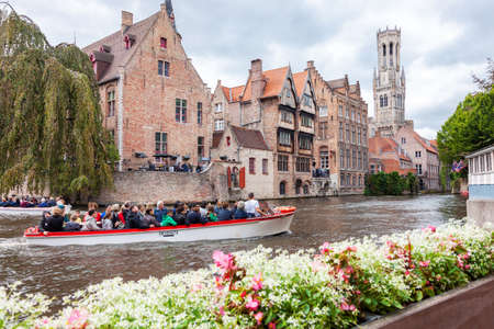 Bruges, Belgium - August 27, 2018: Boat full of tourists in the water canal of picturesque old town of Bruges in the Flemish region of Belgium