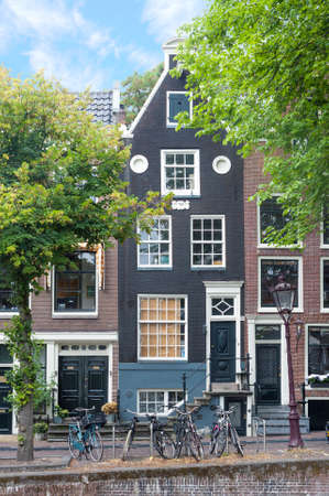 City view of Amsterdam with traditional old town buildings and architecture on bright summer day 写真素材