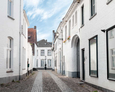 Empty old town street with white painted buildings early in the morning in Thorn, Netherlands