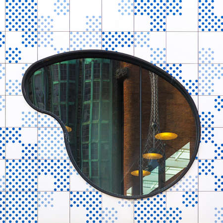 Abstract architectural picture with blue dotted facade, shaped window and industrial reflection