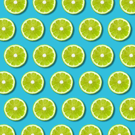 Green lime slices pattern on vibrant turquoise color background. Minimal flat lay food texture 写真素材