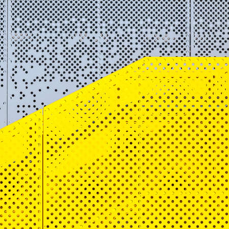 Grey and yellow perforated industrial metal background, abstract dotted texture