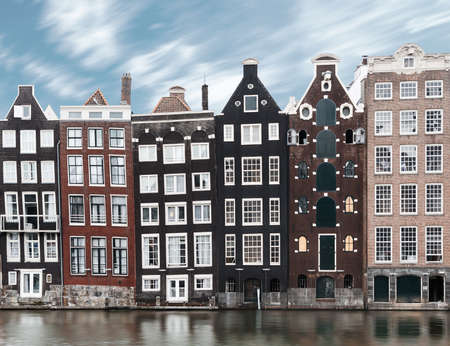 Long exposure picture of traditional Amsterdam old town architecture with typical dutch houses, motion blur on canal water and clouds
