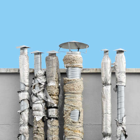 Close up of set of ventilation chimneys with damaged isolation against blue sky