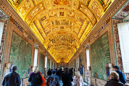 Vatican, Vatican city - December 9, 2017: Wall and ceiling paintings in the Gallery of Maps with tourists wandering arround at the Vatican Museum, Vatican City, Rome