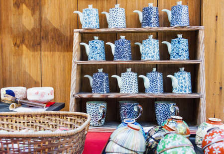 Japanese asian style porcelain for sale in pottery shop in Kyoto, Japan. Decorated tea pots, cups and bowls on handmade wooden stands