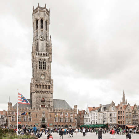 Bruges, Belgium - 27 August, 2018: Central market square (Grote markt) and Belfort tower with tourists wandering around in Bruges, Belgium on cloudy and gloomy day 報道画像