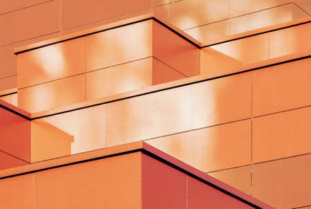 Orange colored geometric background of metal building facade. Abstract architectural shapes and lines Stock fotó