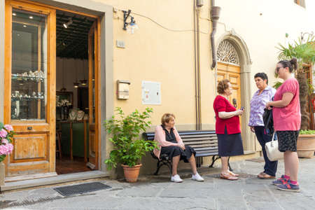 Castellina in Chianti, Italy - 30 June, 2016: Group of local middle age and senior women socializing on the street in the old italian town of Castellina in Chianti on warm summer day