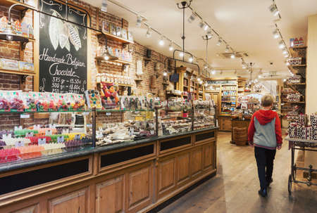Bruges, Belgium - 27 August, 2018: Traditional cozy Belgian chocolate store interior with variey of candies and sweets to choose from in the old town of Bruges, Belgium