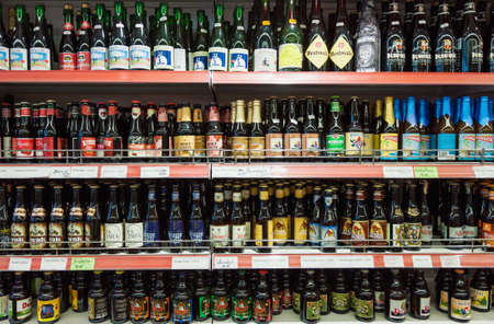 Bruges, Belgium - 27 August, 2018: Variety of Belgian crafted beers for sale in a shop, branded bottles on shop shelf display in supermarket in Bruges, Belgium