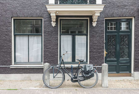 Typical Amsterdam old town street view in Netherlands with old doors and windows and vintage bicycle, front view horizontal daytime picture 写真素材