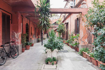 Typical weathered historical residential yard in the old town of Italian capital Rome with a lot of tropical potted flowers