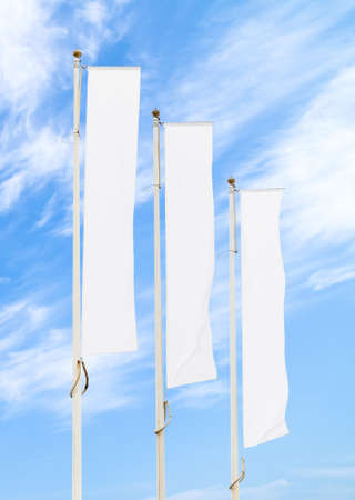 Three blank white flags on flagpoles against cloudy blue sky with perspective, corporate flag mockup to ad logo, text or symbol, company identity flag template with copy space 写真素材