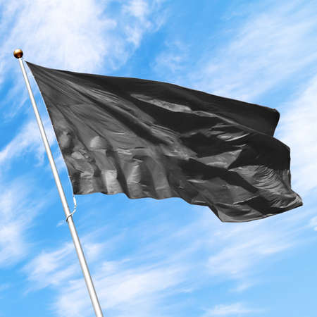Black flag waving in the wind against blue cloudy sky. Perfect mockup to add any logo, symbol or sign 写真素材