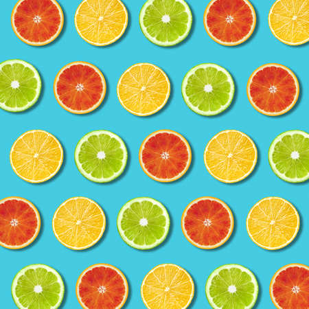 Multicolored vibrant lemon, green lime and red orande slices pattern on turquoise background. Minimal flat lay top view food texture 写真素材