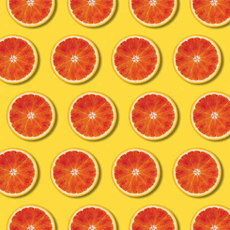 Red orange slices pattern on yellow color background. Minimal flat lay top view food texture 写真素材