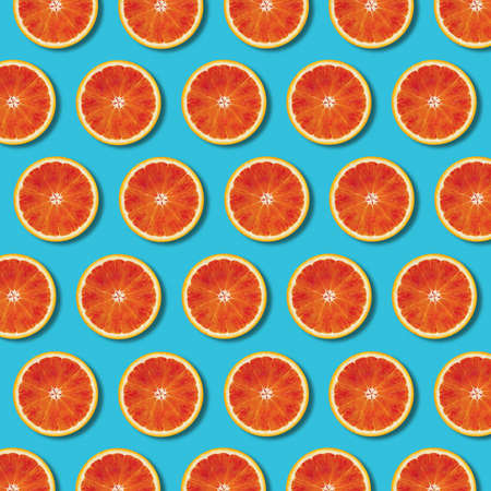 Red orange slices pattern on vibrant turquoise color background. Minimal flat lay top view food texture