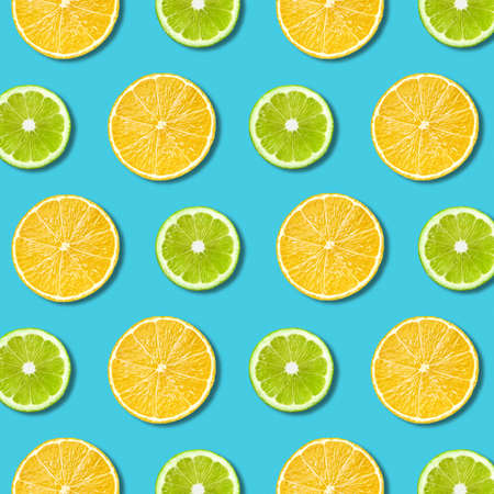 Vibrant lemon and green lime slices pattern on turquoise color background. Minimal flat lay top view food texture