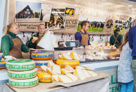 Delft, Netherlands - August 25, 2018: Sellers selling traditional Dutch cheese in street market in Delft, Netherlands