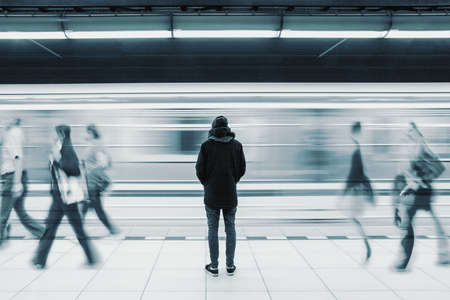 Long exposure picture with lonely young man shot from behind at subway station with blurry moving train and walking people in background 写真素材
