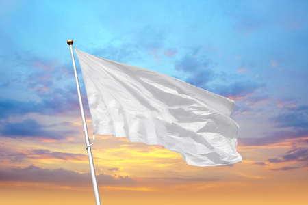 Blank white flag on pole waving in the wind in the background of cloudy sky at sunset. Colorful outdoor picture with empty flag mockup 写真素材