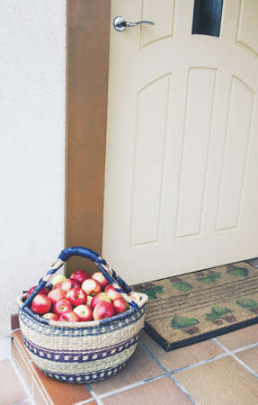 Basket of fresh red apple fruits standing at doorway, real life outdoor vertical picture