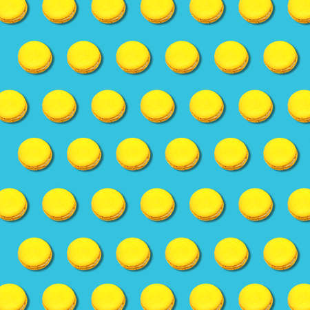 Vibrant geometric abstract pattern of yellow macaroons on turquoise background, flat lay colorful food texture