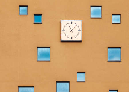 Building facade with random wndows and clock, abstract architectural wall Stock Photo