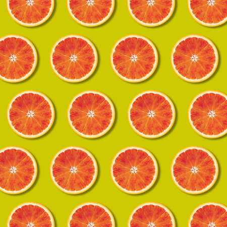 Geometric red orange fruit slices pattern on green color background. Minimal flat lay, top view food texture  写真素材