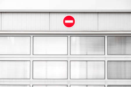 No entry traffic sign on gray industrial wall, minimalist architecture with warning road sign, red color pop up